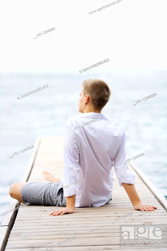 Stock Photo: Back view of a young man sitting and relaxing in a Pier.