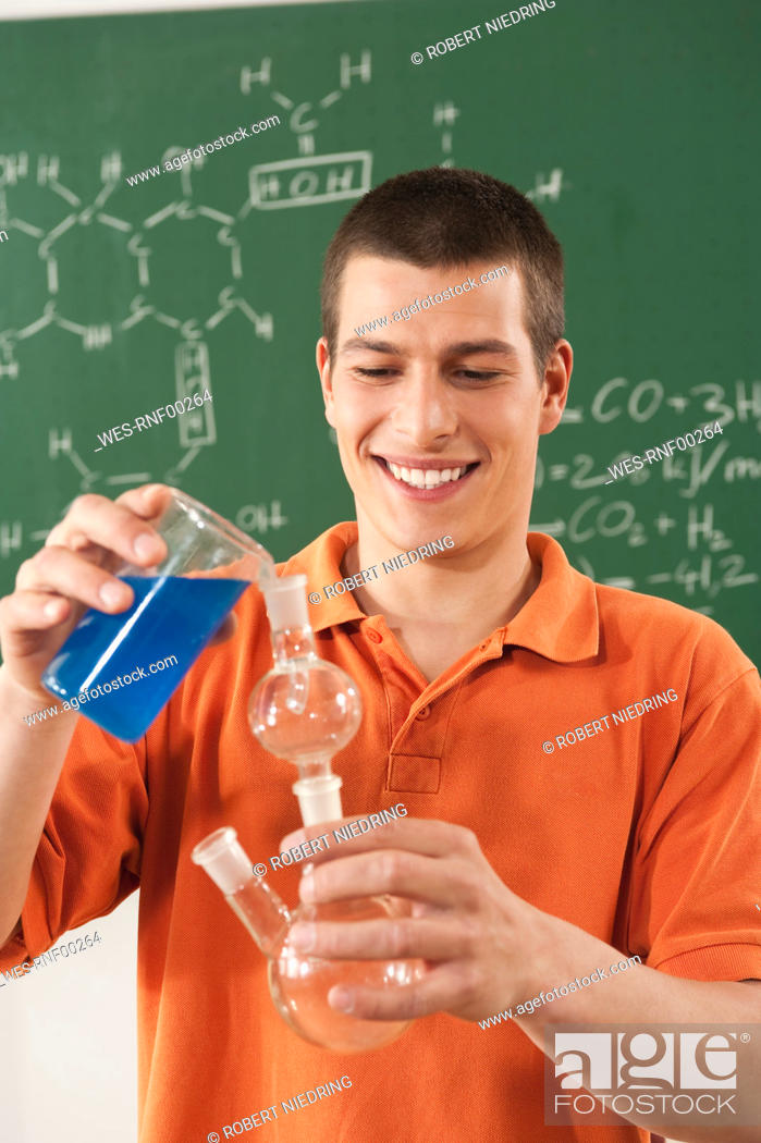 Stock Photo: Germany, Emmering, Young man doing experiment, smiling.