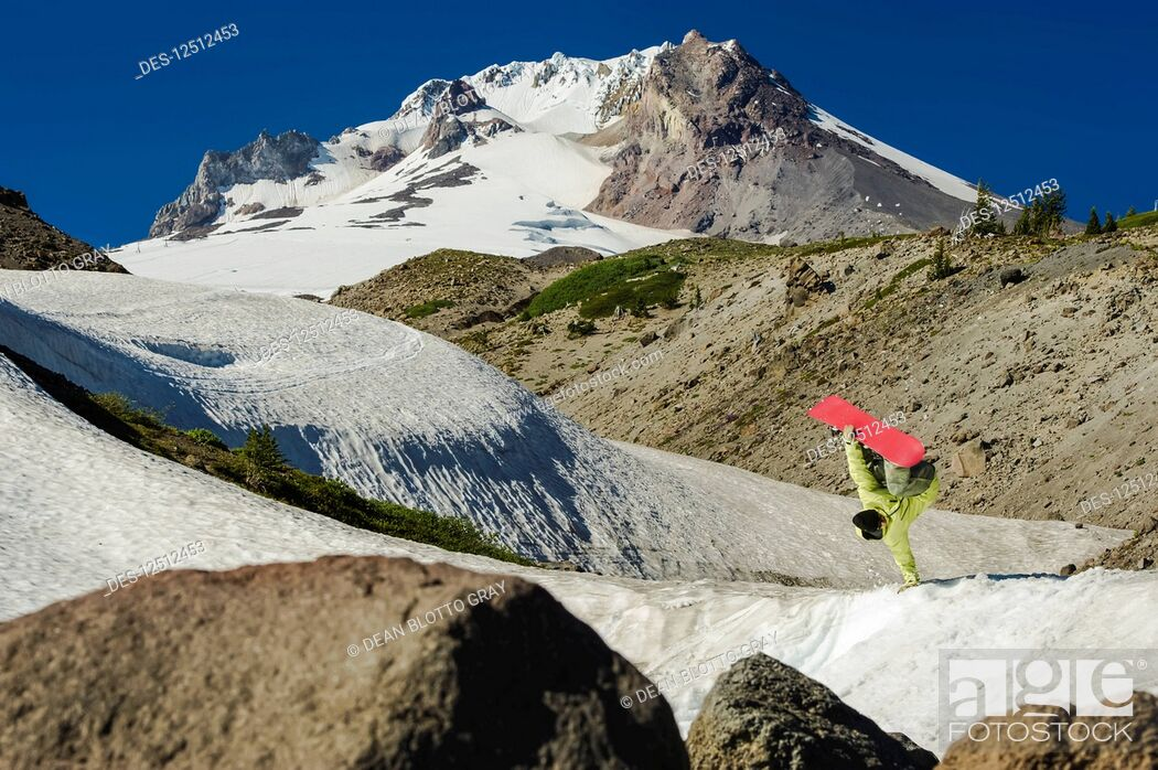 Imagen: A professional, freeriding snowboarder flips mid-air on a snowy slope with rugged mountain peaks; British Columbia, Canada.