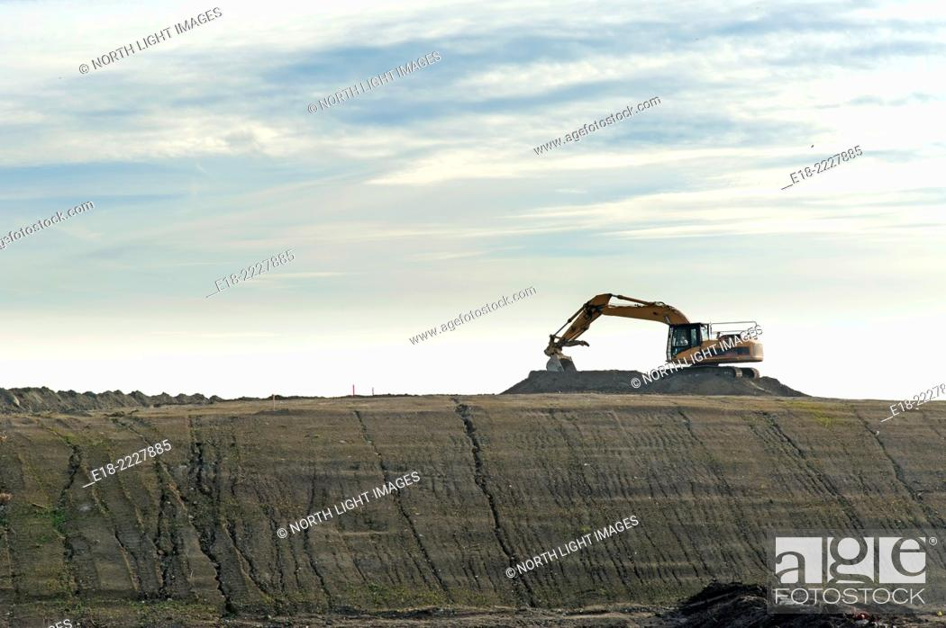 Imagen: Canada, BC, Delta. Excavator silhouetted against sky on construction site preload, River Road.