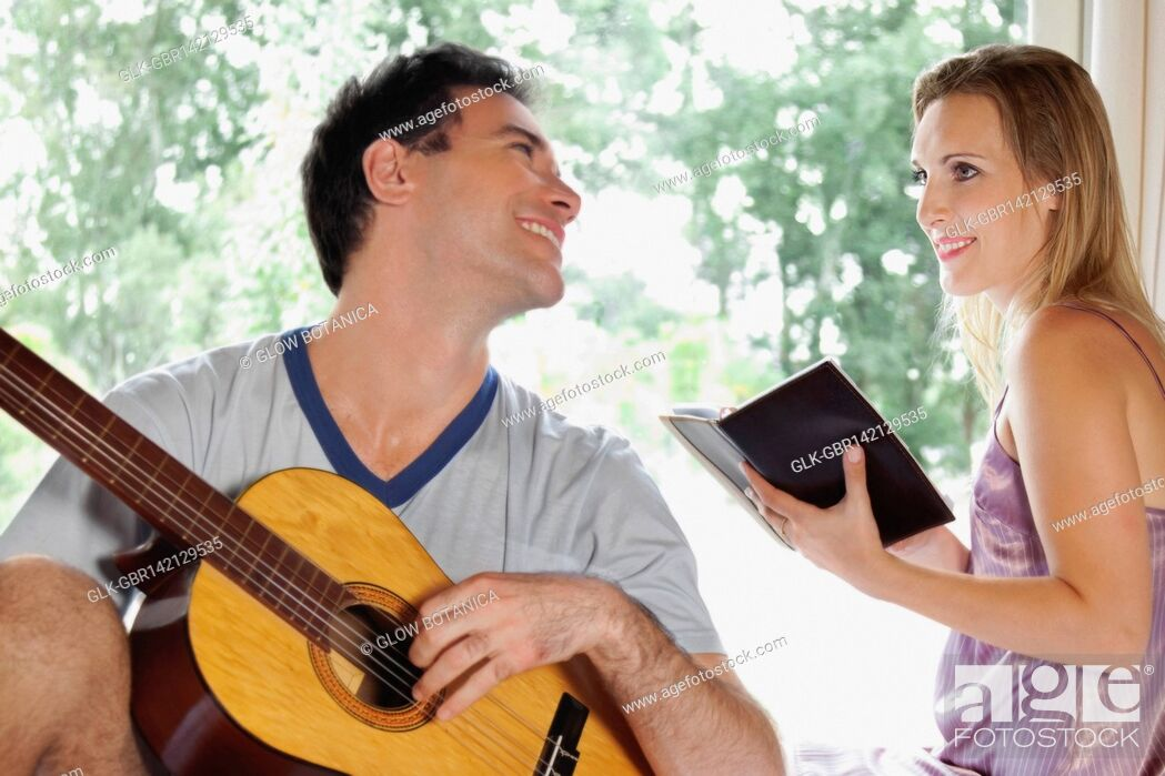 Stock Photo: Man playing a guitar with his wife holding a book.