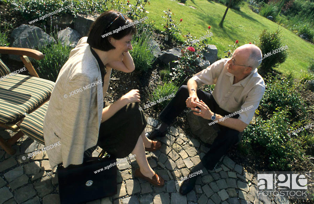 Stock Photo: A senior, businessman, 45-50 50-55 55-60 years old, and a woman, businesswoman, 40-45 45-50 years old, sitting in a summerly garden, talking.