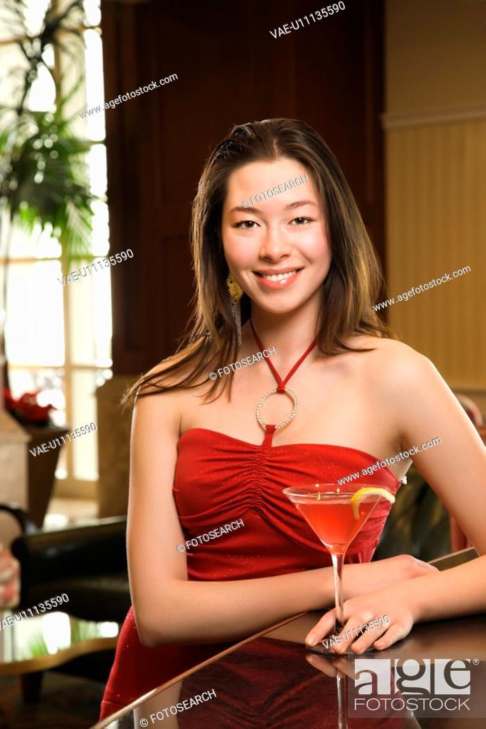 Stock Photo: Taiwanese mid adult woman in red dress smiling and standing at bar with drink.