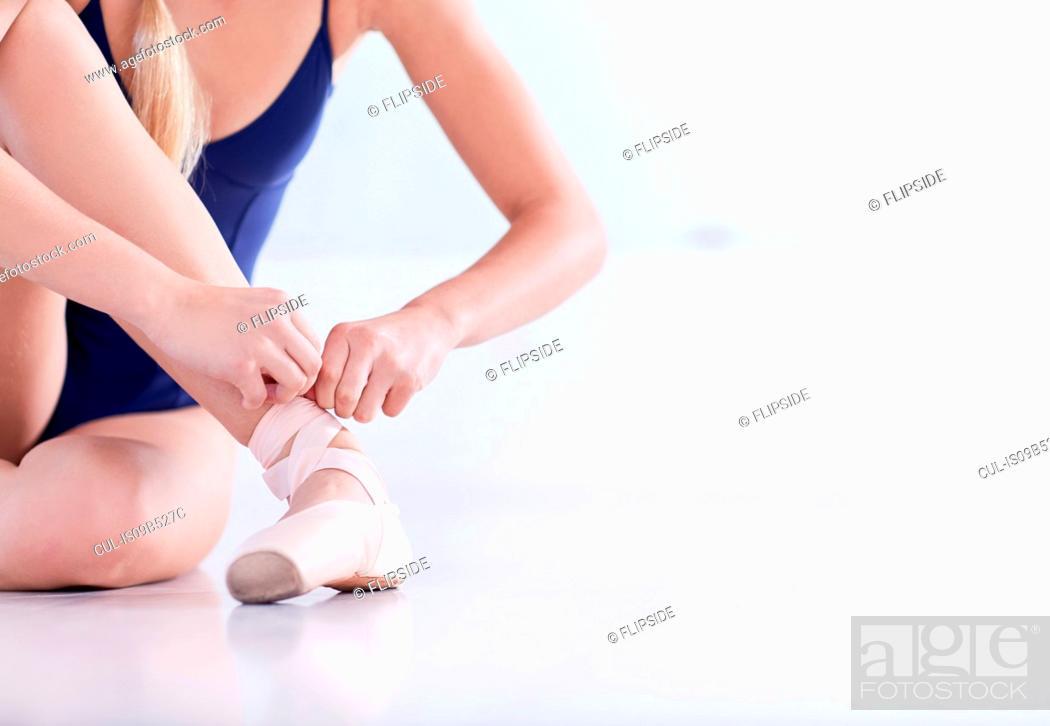 Stock Photo: Cropped shot of female ballet dancer sitting on dance studio floor tying ballet slipper.
