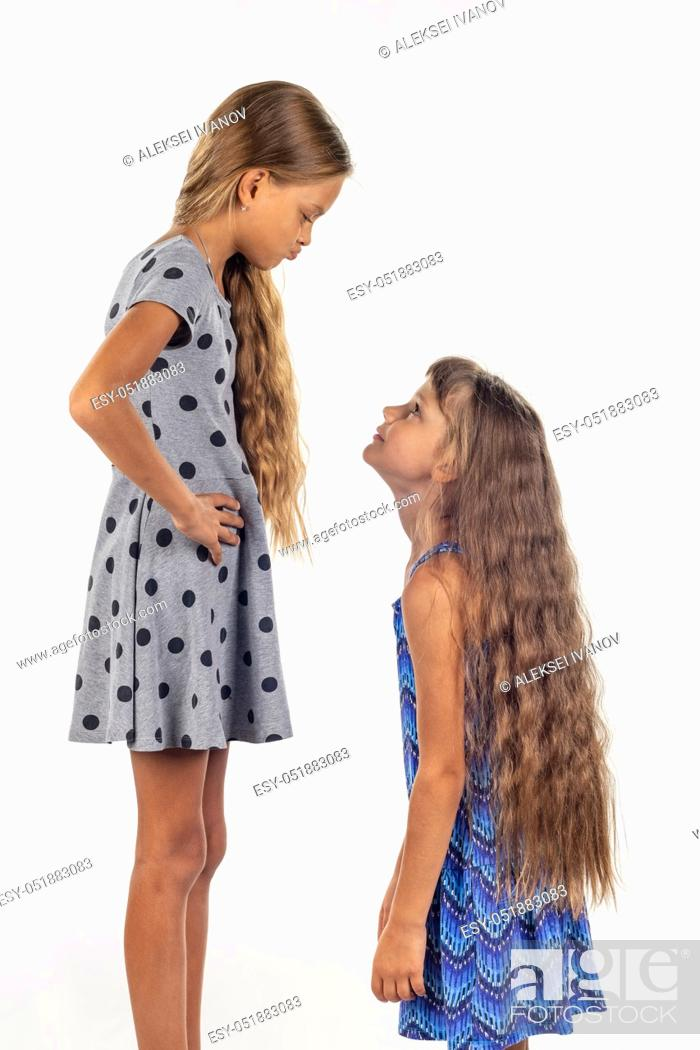 Stock Photo: Two girls of different stature, one stood on a chair and became even taller.