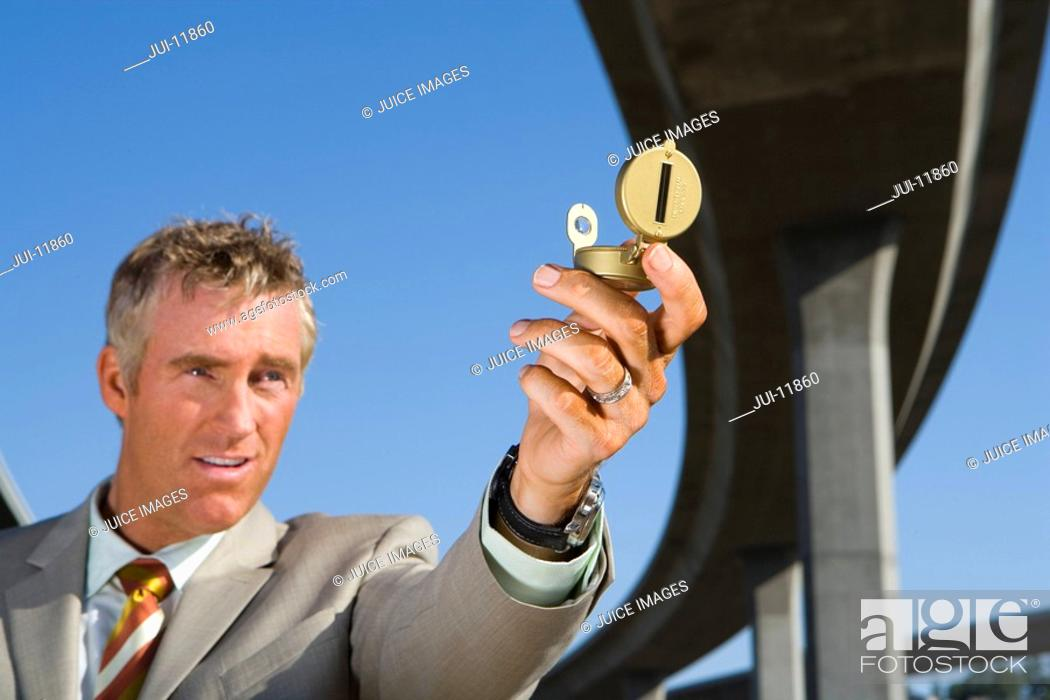 Stock Photo: Businessman holding up compass beneath overpass, low angle view.