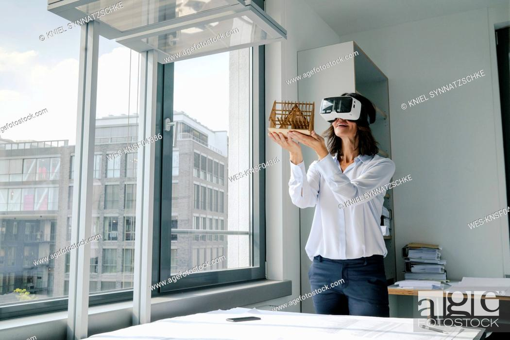 Stock Photo: Woman holding architectural model of house, using VR glasses.