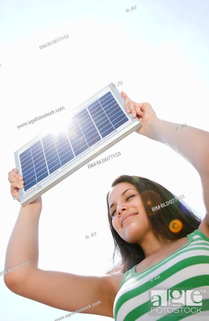 Stock Photo: Mixed race woman holding solar panel.