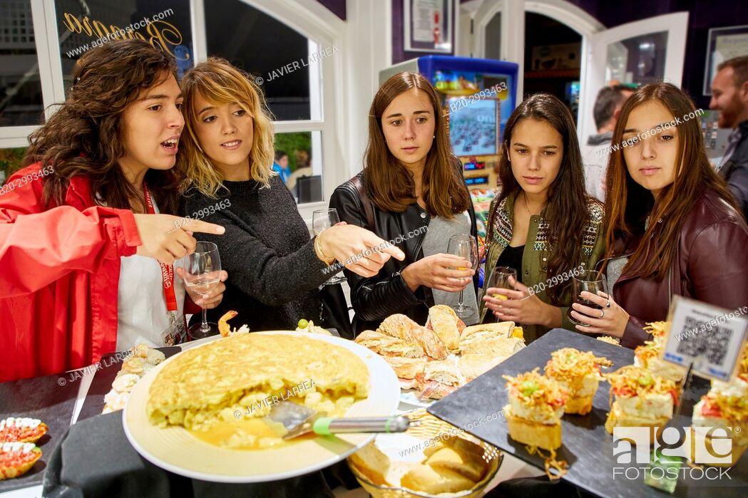 Stock Photo: Group of tourists and guide making a tour of the city, Eating pintxos, Donostia, San Sebastian, Gipuzkoa, Basque Country, Spain, Europe.