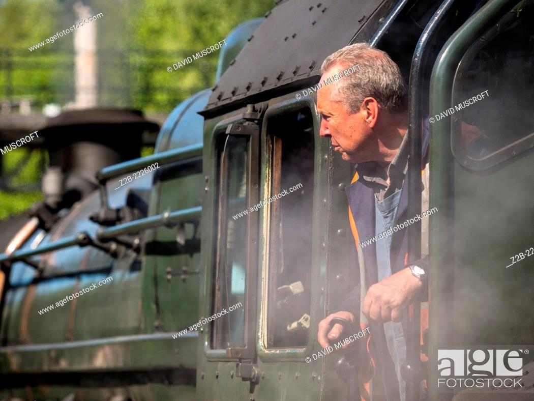 Stock Photo: Train driver of a vintage steam locomotive at Grosmont station on the North Yorkshire Moors Railway, near Whitby, North Yorkshire, UK.