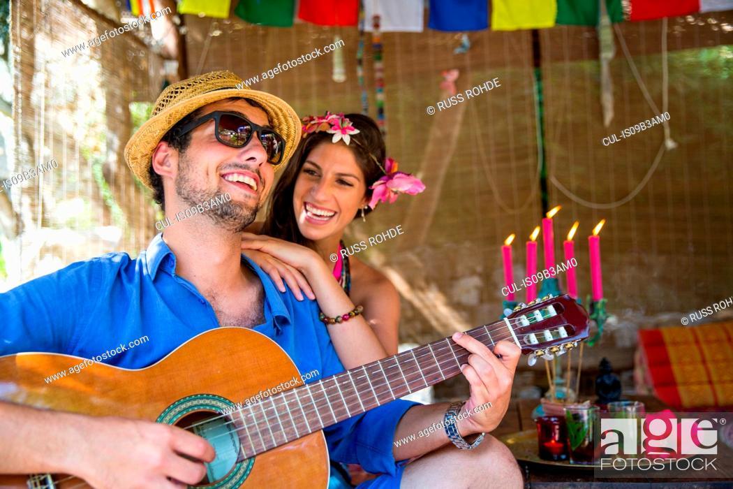 Photo de stock: Young couple playing guitar smiling.