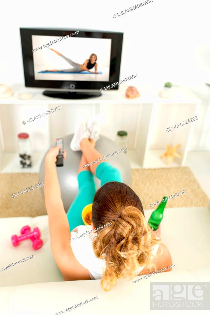 Stock Photo: Lazy woman in sport clothing sitting front of the TV and doesn't wont to exercise.