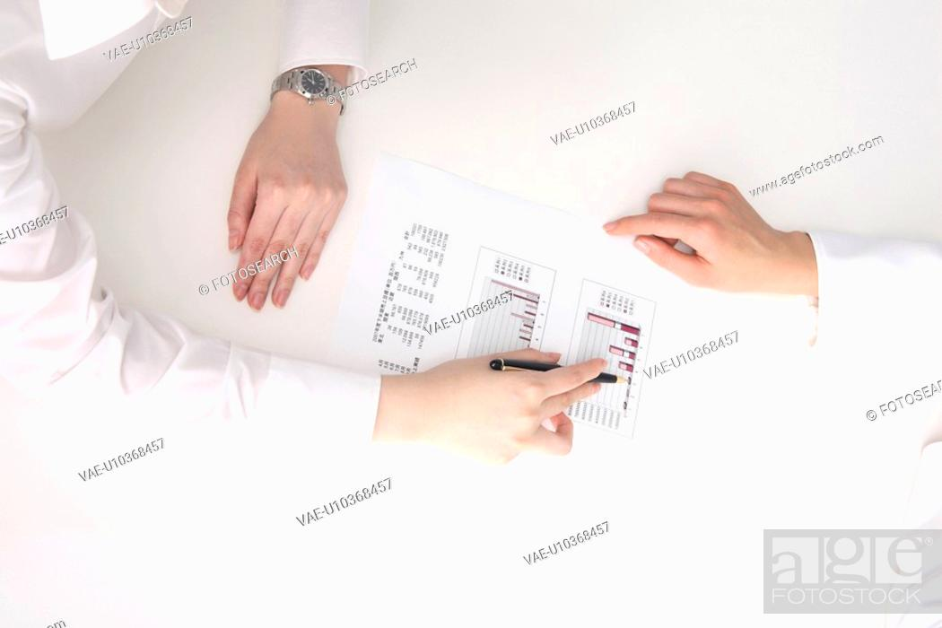 Stock Photo: Hand of woman pointing at a document with a pen, and explaining it.