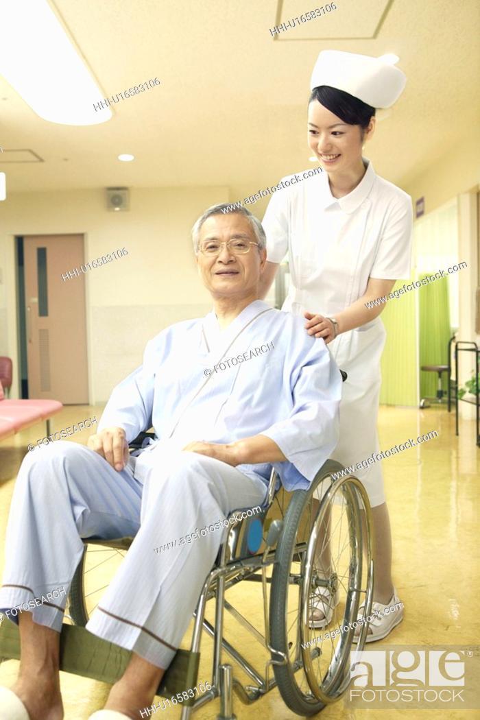 Stock Photo: Nurse pushing the wheelchair.