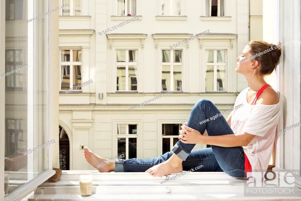 Stock Photo: Germany, Berlin, Young woman sitting at open window.