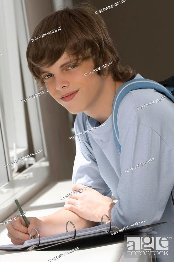 Stock Photo: Portrait of a teenage boy writing on spiral notebook and smiling.