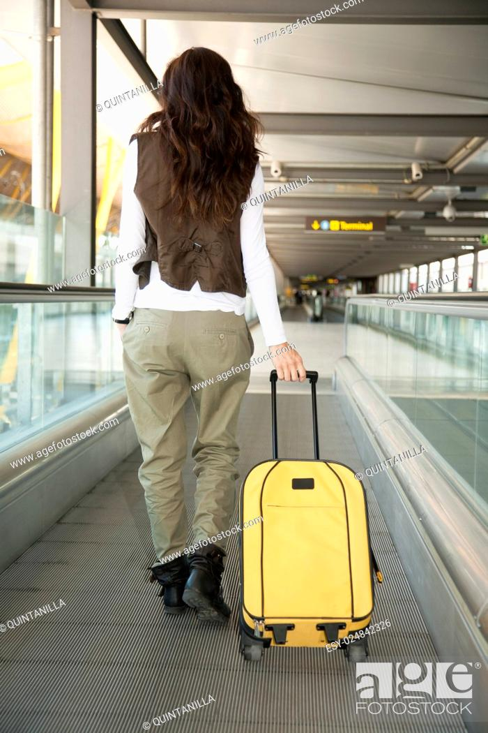 Stock Photo: woman with vest walking with yellow suitcase at walkway inside airport hall.