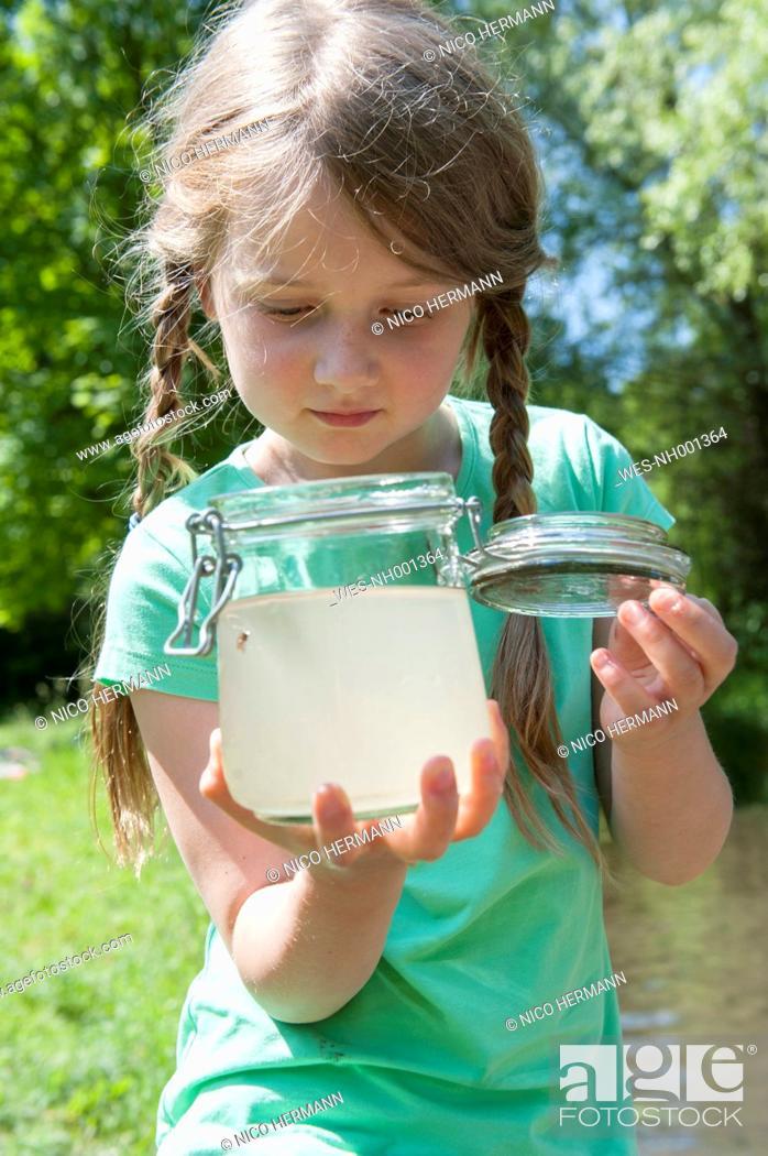 Stock Photo: Germany, Bavaria, Munich, Girl holding glass jar, close up.