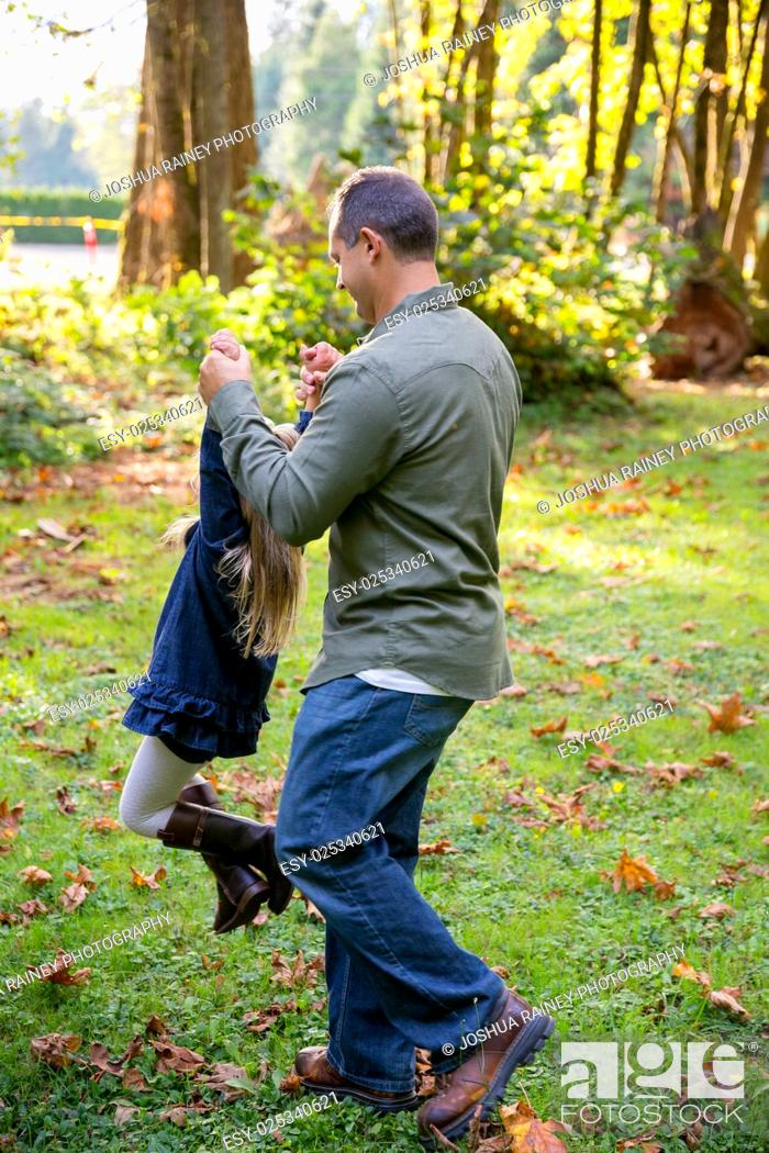 Stock Photo: Dad swinging his young daughter around by the arms while playing and having fun at a nature park.