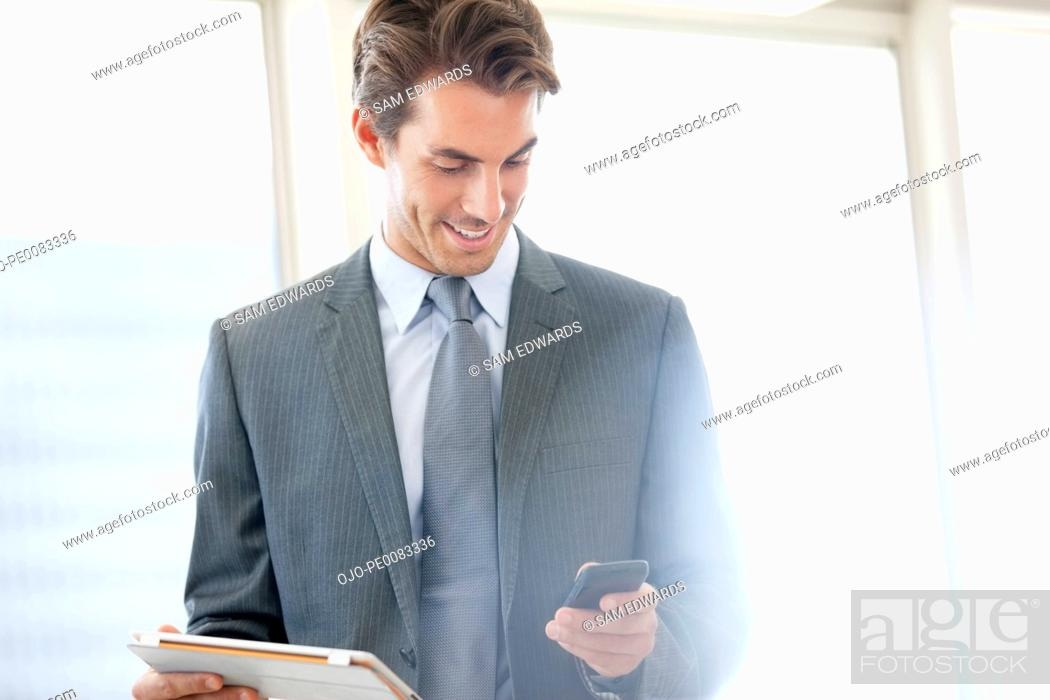 Stock Photo: Smiling businessman holding digital tablet and checking cell phone.