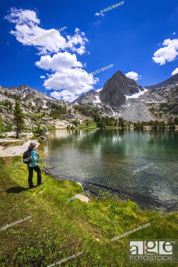 Stock Photo: Hiker on the shore of Treasure Lake, John Muir Wilderness, Sierra Nevada Mountains, California USA.
