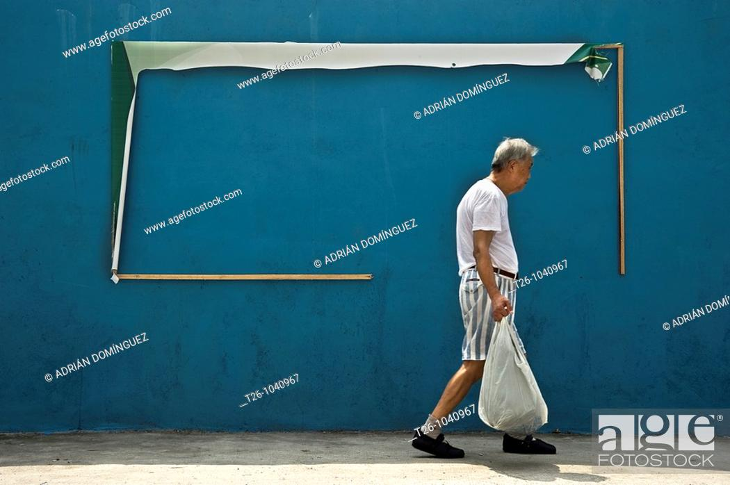 Stock Photo: A man walks down the street in front of a billboard. Shanghai, China.