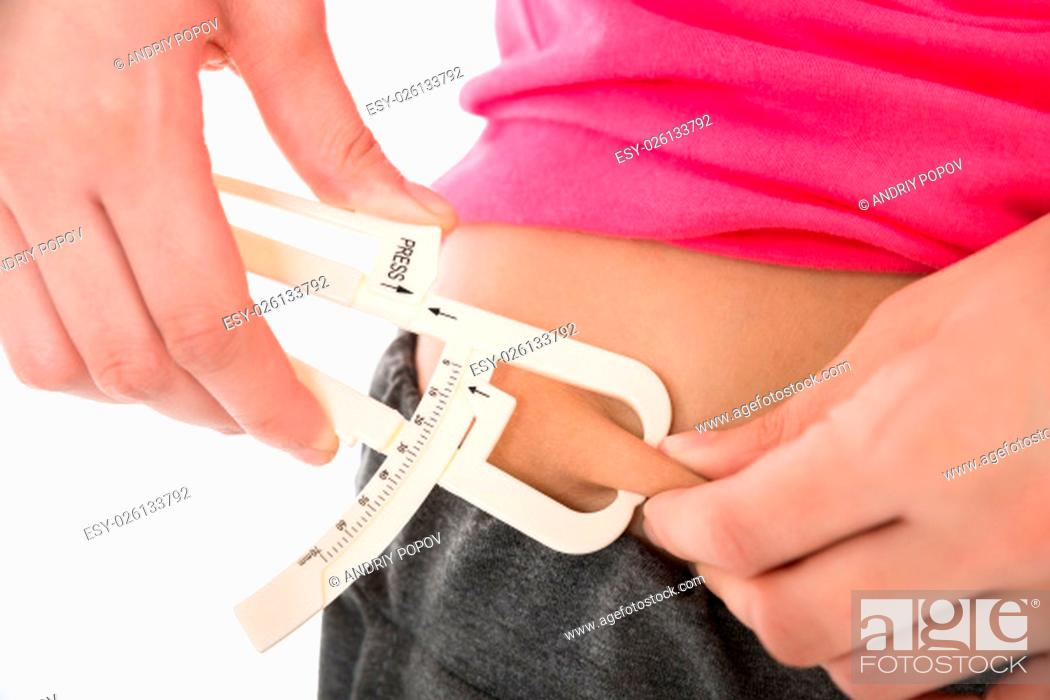 Stock Photo: Midsection of young woman measuring fats with caliper against white background.