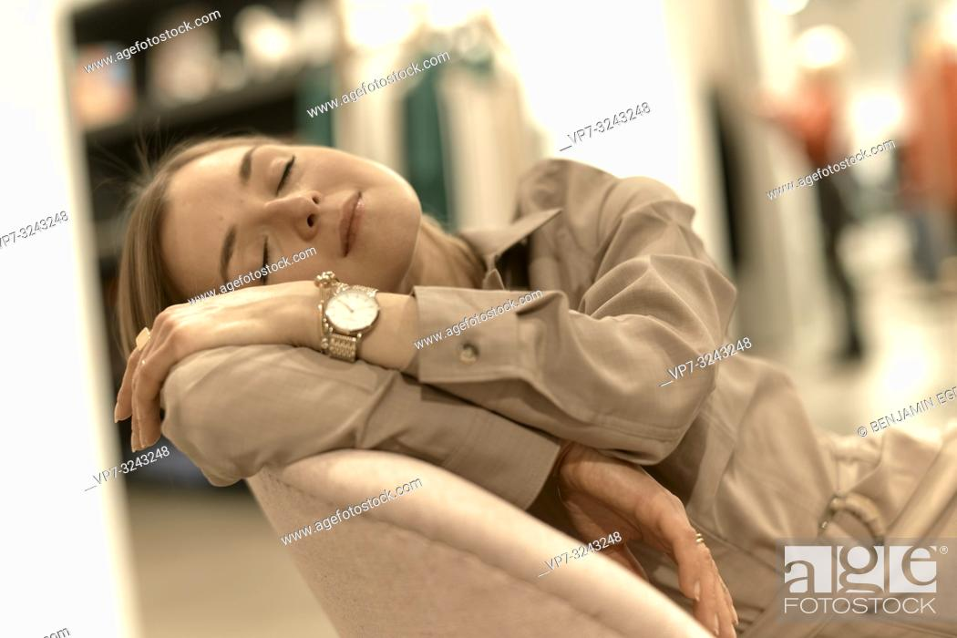 Stock Photo: exhausted fashionable woman relaxing in armchair, sleepy, closed eyes, tired, in Munich, Germany.