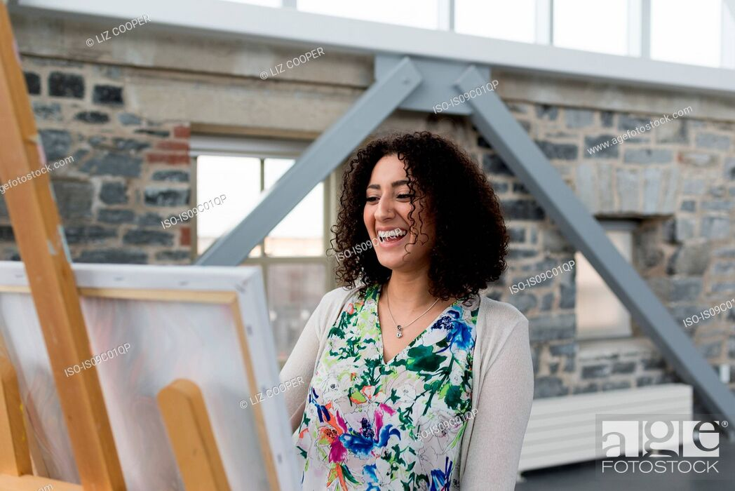 Imagen: Young female painter laughing whilst painting canvas in studio.