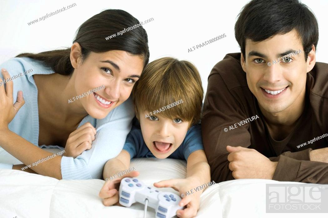 Stock Photo: Little boy playing video game, parents watching.