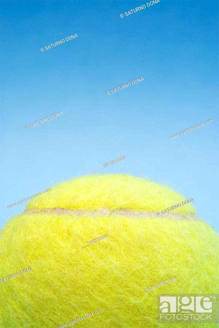 Stock Photo: yellow tennis ball against blue sky.