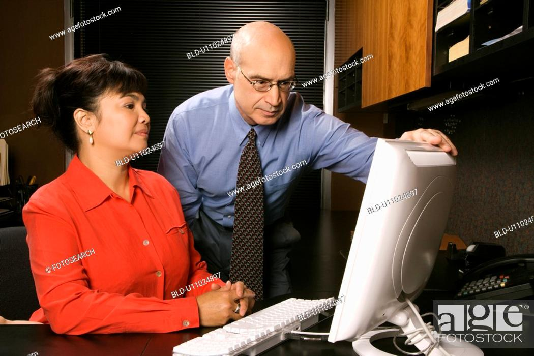 Stock Photo: Businessman and businesswoman in office looking at computer monitor.