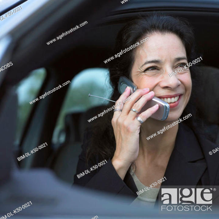 Stock Photo: Businesswoman talking on her cell phone inside car.