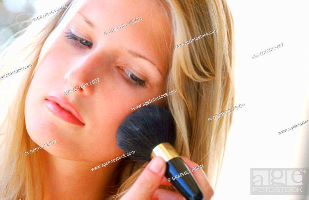 Stock Photo: Young woman applying color on her cheek.
