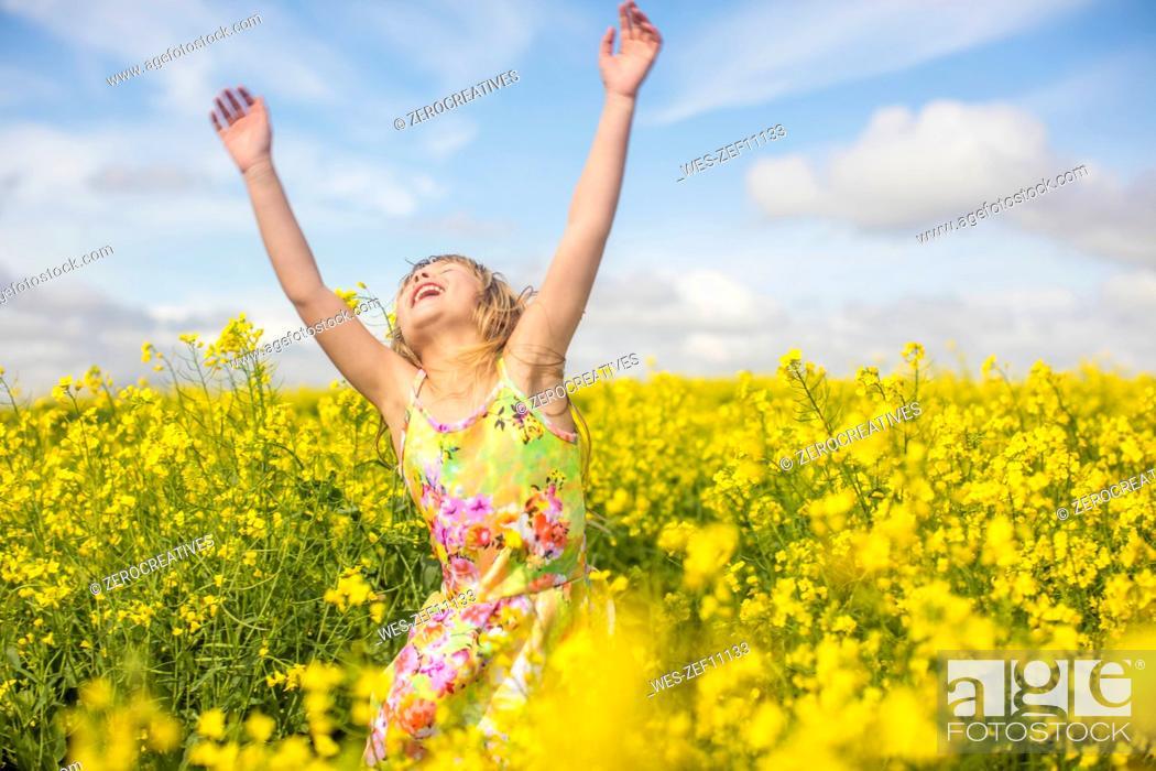 Stock Photo: Little girl dancing in rape field.