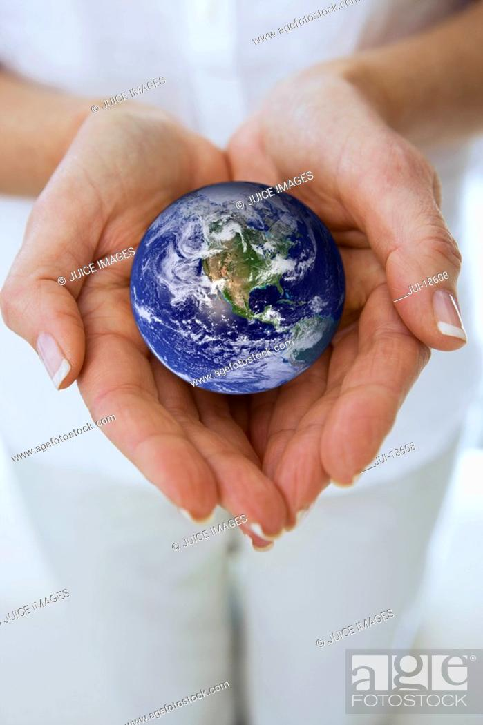 Stock Photo: Close up of womanÆs hands cupping miniature globe.
