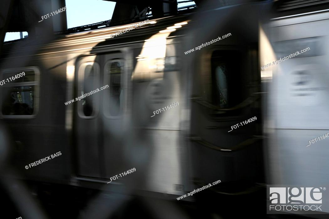 Stock Photo: American public transport train passing by with blurred wire mesh fence in foreground.