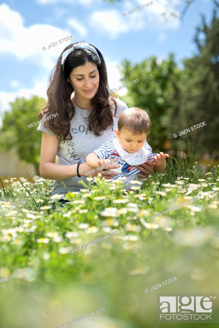 Stock Photo: Mother and baby son on blossoming field of flowers in spring.