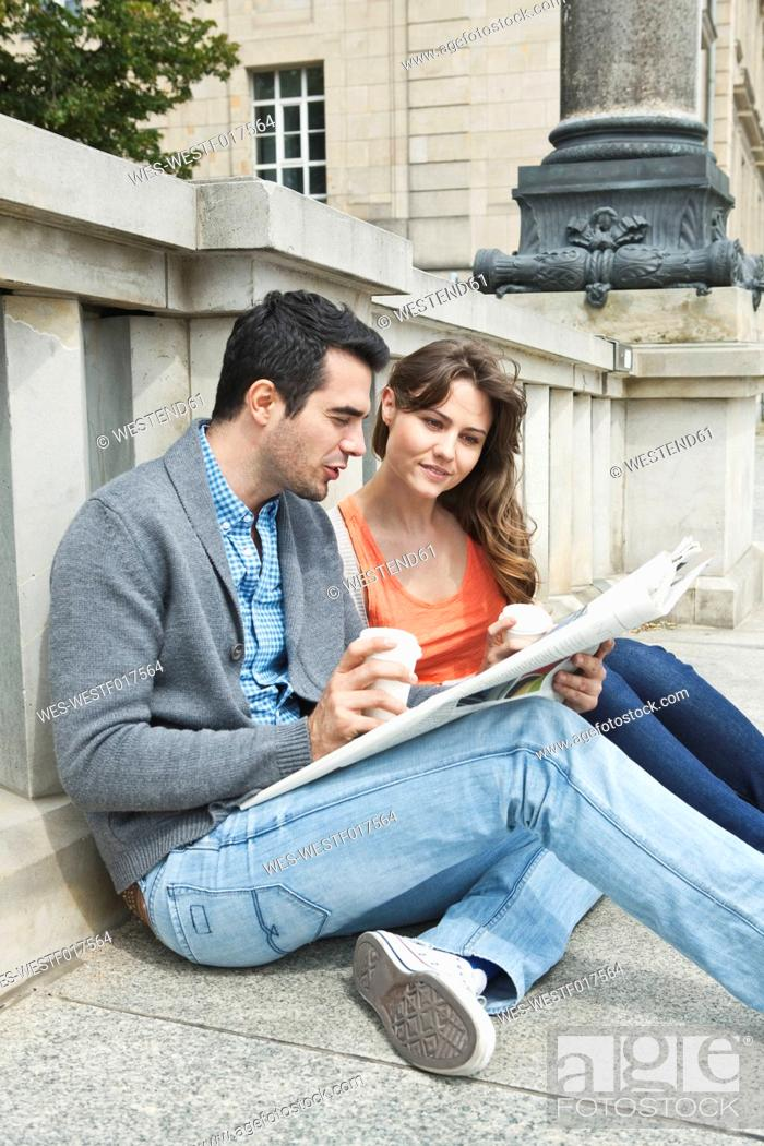Stock Photo: Germany, Berlin, Couple sitting on sidewalk and reading newspaper.