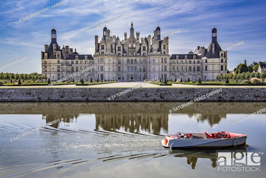 Stock Photo: Chambord Castle with some people boating on the canal that surrounds it.