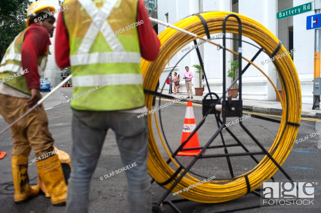 Imagen: Singapore, Republic of Singapore, Asia - Two workers are laying cables on a road in the central business district.