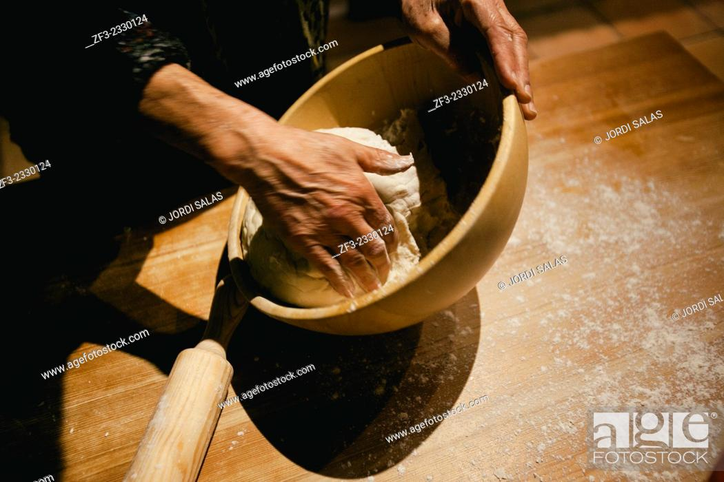 Stock Photo: Hands kneading wheat bread dough on a wooden table.
