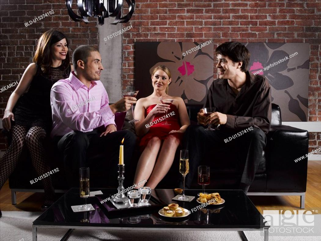 Stock Photo: Four friends with drinks at party.