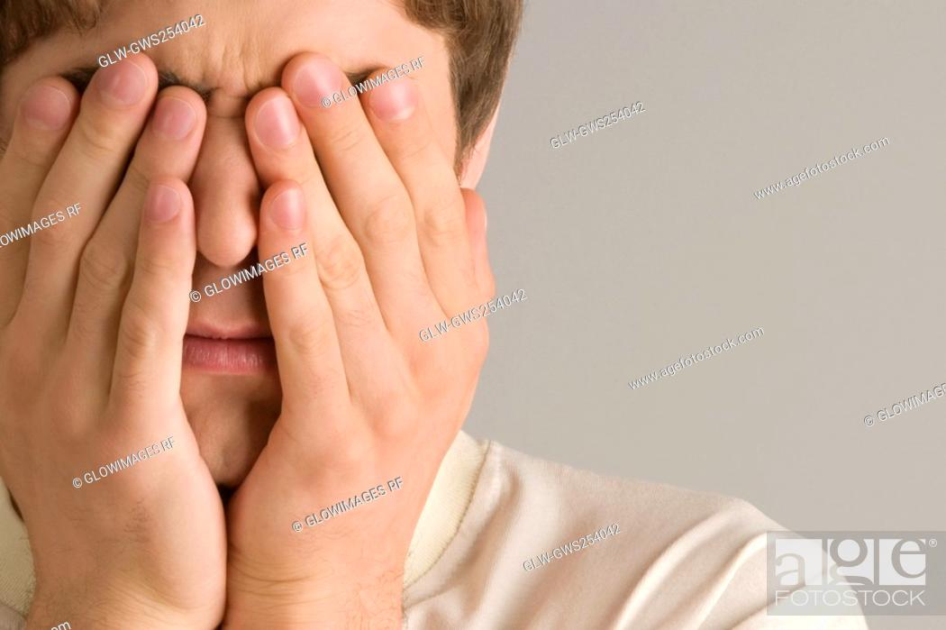 Stock Photo: Close-up of a young man covering his eyes with his hands.