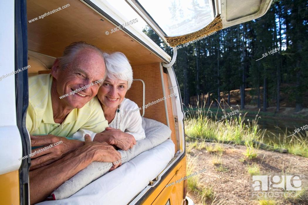 Stock Photo: Senior couple lying in back of camper van, smiling, portrait, close-up.