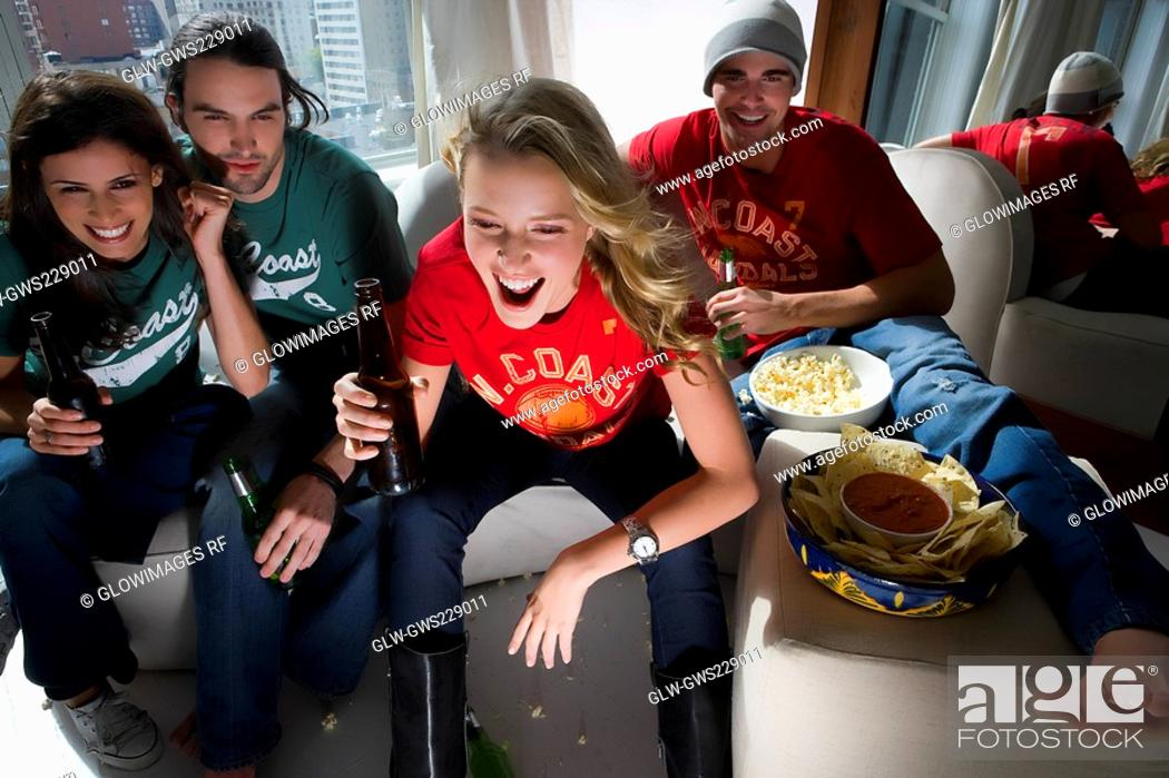 Stock Photo: Two young couples sitting on a couch and drinking beer.