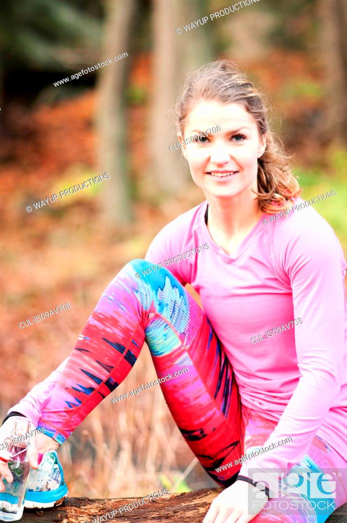Stock Photo: Young woman wearing sportswear, sitting with leg raised, looking at camera smiling.
