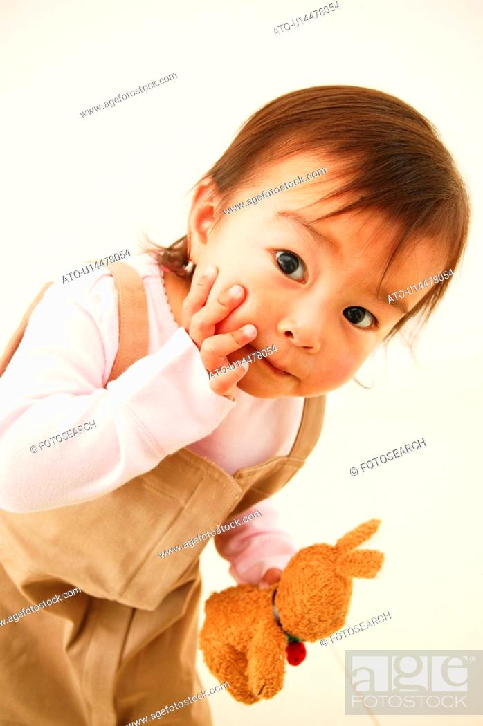 Stock Photo: A Baby Girl holding a rabbit doll.