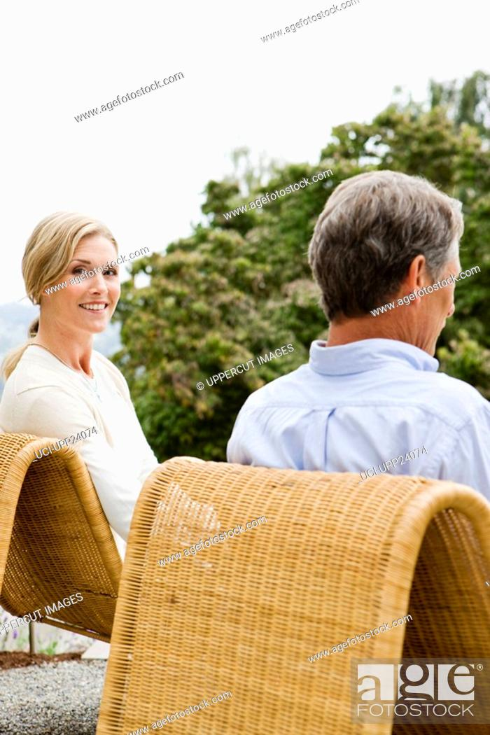 Stock Photo: Portrait of couple sitting on patio chairs.