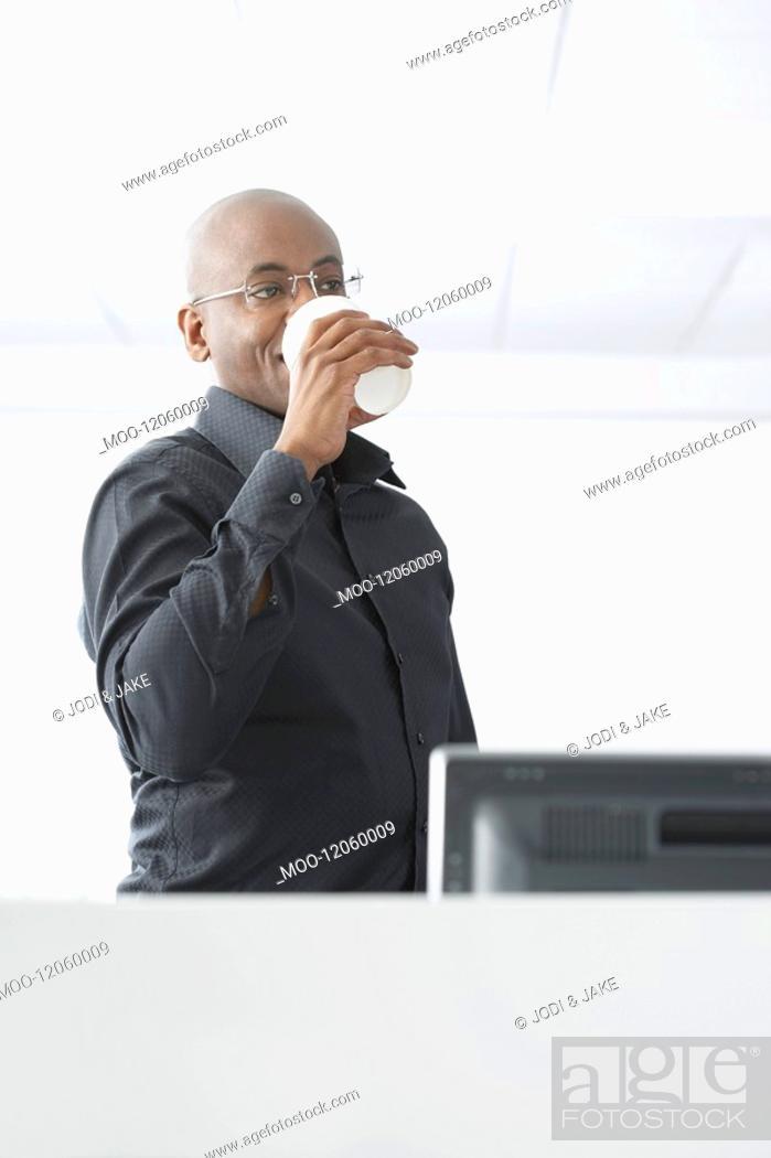 Stock Photo: Office worker drinking coffee in office.